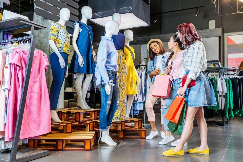 Wielokulturowe modniś dziewczyny z torba na zakupy w zakupy centrum handlowym obrazy royalty free