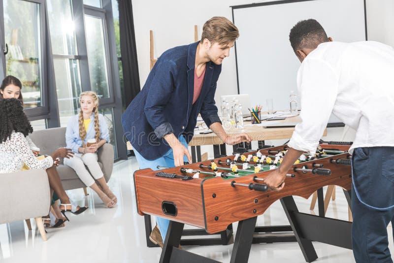 wielokulturowi biznesmeni bawić się stołowego futbol podczas gdy bizneswomany ma rozmowę podczas przerwy zdjęcie stock