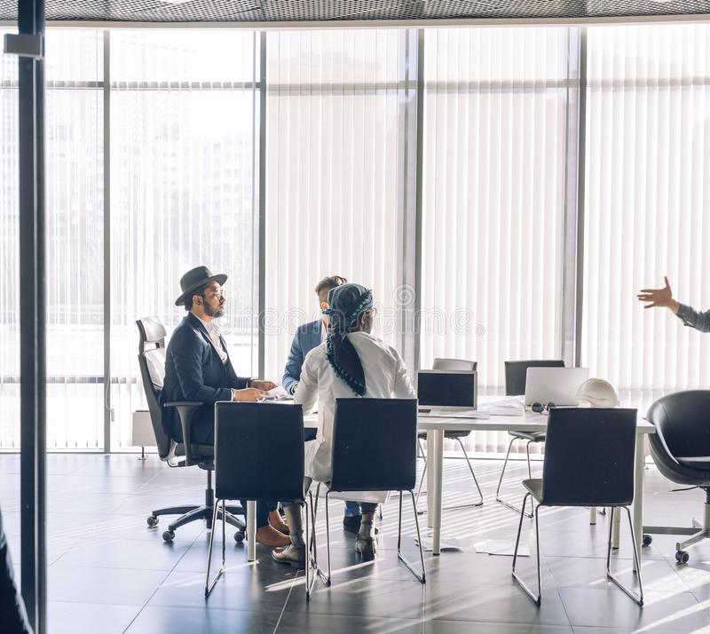 Wielokulturowi ludzie biznesu spotyka przy nowożytnymi panoramicznymi okno biurowymi zdjęcia stock