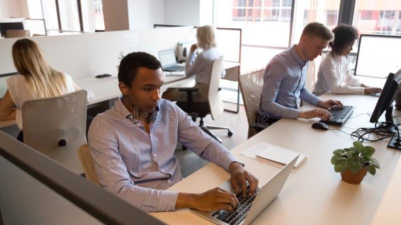 Wielokulturowi pięcioliniowi ludzie biznesu siedzi przy biurkami pracuje w biurze fotografia royalty free