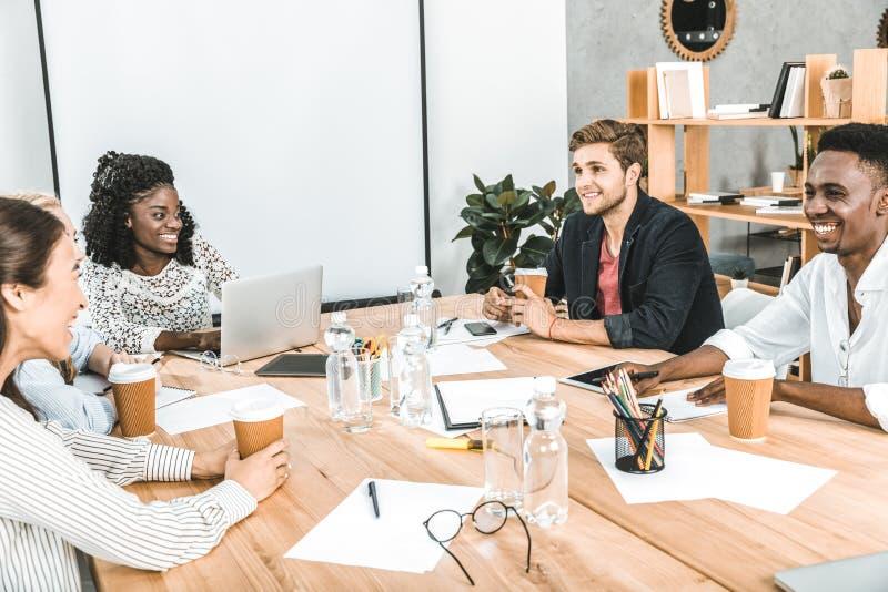 wielokulturowi uśmiechnięci biznesmeni dyskutuje strategię biznesową podczas konwersatorium zdjęcie royalty free