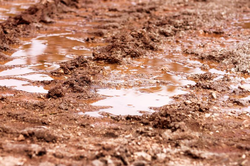 Wielspoor op weg, vulklei en modder na regen Sporen op grond van tractor, graafwerktuig, auto, automobielbandsporen op modderige  royalty-vrije stock foto's