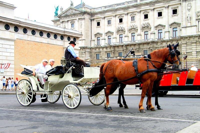 Wien, Österreich, ältere Touristen fahren auf einen gehenden Trainer und hören auf die Geschichte eines Kutscherführers stockfoto