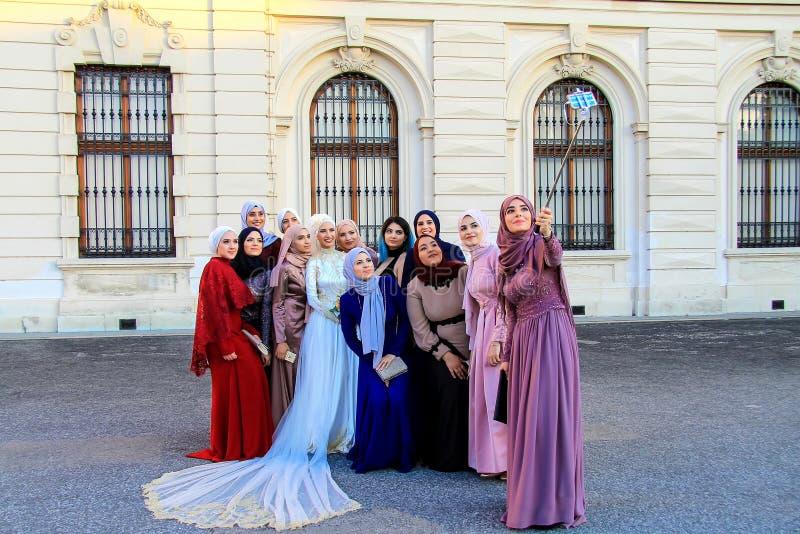Wien Österrike, härliga flickor i muslimsk kläder och bröllopsklänning fotograferas nära slotten, Europa arkivbild