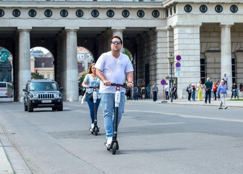 WIEN ÖSTERRIKE - MAJ 26: Modern stadstransport - folk som rider gatorna på hyrda elektriska sparkcyklar vid fågeln i Wien, Österr arkivfoto