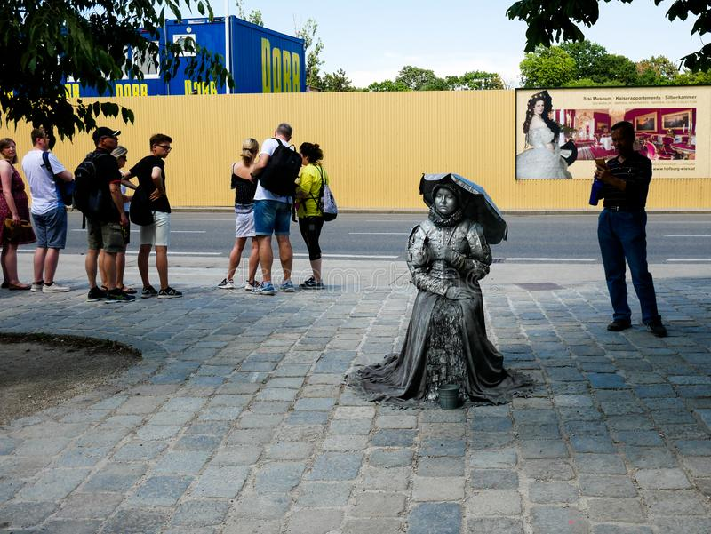 Wien/Austria - june 4 2019: an Street actress outside of Schonbrunn palace in vienna with a gray dress looking as an sculpture. With tourists taking photos stock image