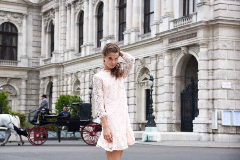 Wien påstår teatern Burgtheater, Österrike En flicka i en rosa klänning står på bakgrunden av byggnaden royaltyfri bild