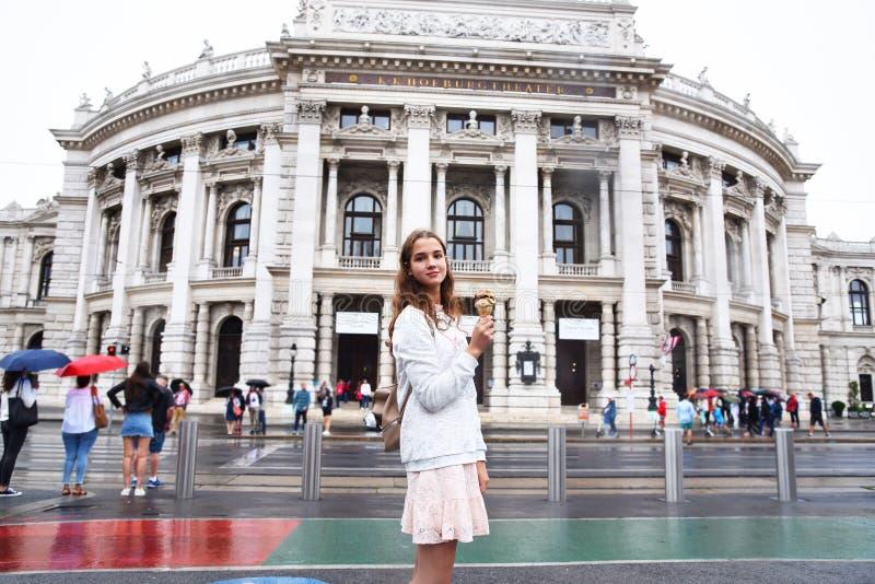 Wien p?st?r teatern Burgtheater, ?sterrike En flicka i en rosa kl?nning st?r p? bakgrunden av byggnaden royaltyfri bild