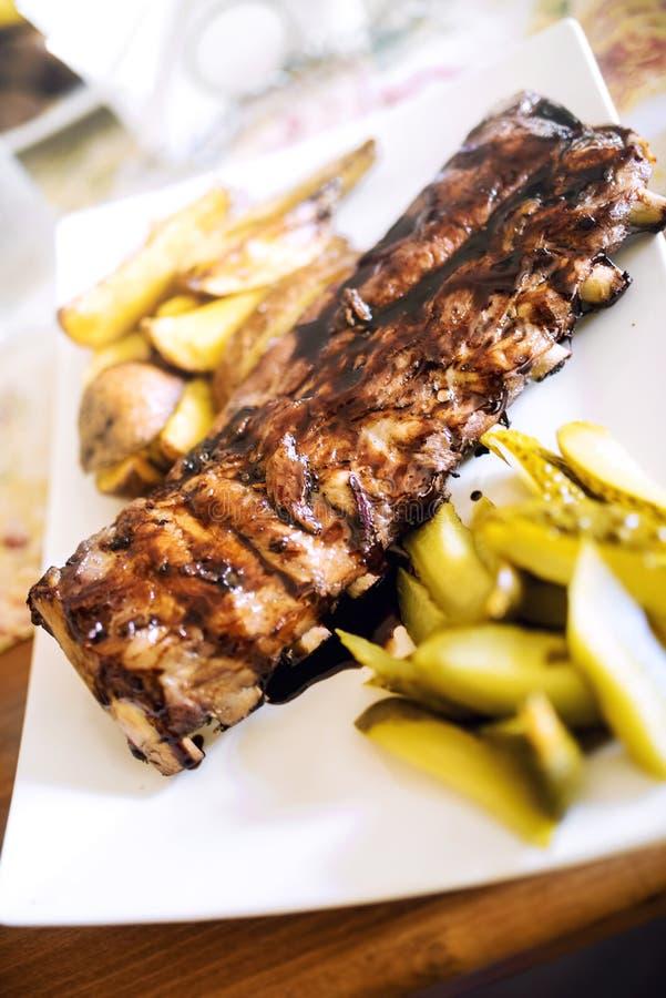Wieprzowina dodatkowi ziobro z grilla kumberlandem, złotymi grulami i zalewami, Główny naczynie przy restauraci, wołowiny lub wie obraz stock