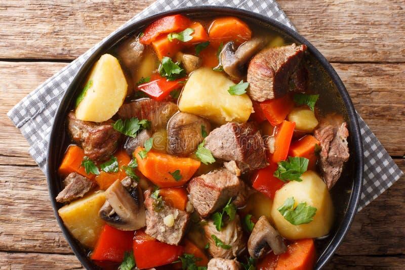 Wieprzowina gulasz z pieczarkami, grulami, marchewkami i pieprzami w górę talerza, dalej horyzontalny odg?rny widok obrazy stock