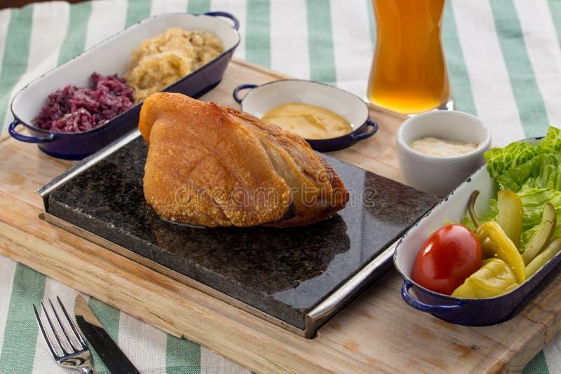 Wieprzowina knykcia pieczeń słuzyć z kapustą i bejcującymi warzywami, tradycyjny Niedziela lunchu gościa restauracji posiłek zdjęcie stock