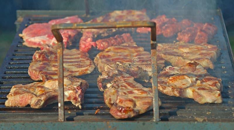 Wieprzowina kotleciki piec na grillu piec na grillu z dymem wokoło fotografia stock