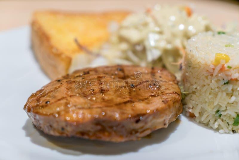 Wieprzowina stek z sałatką i ryż na białym naczyniu w restauraci obrazy royalty free