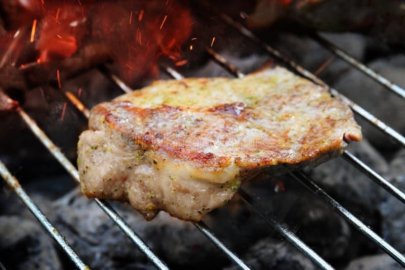Wieprzowiny szyi stek na grilla grillu z rozjarzonym węgla drzewnego briq obrazy stock