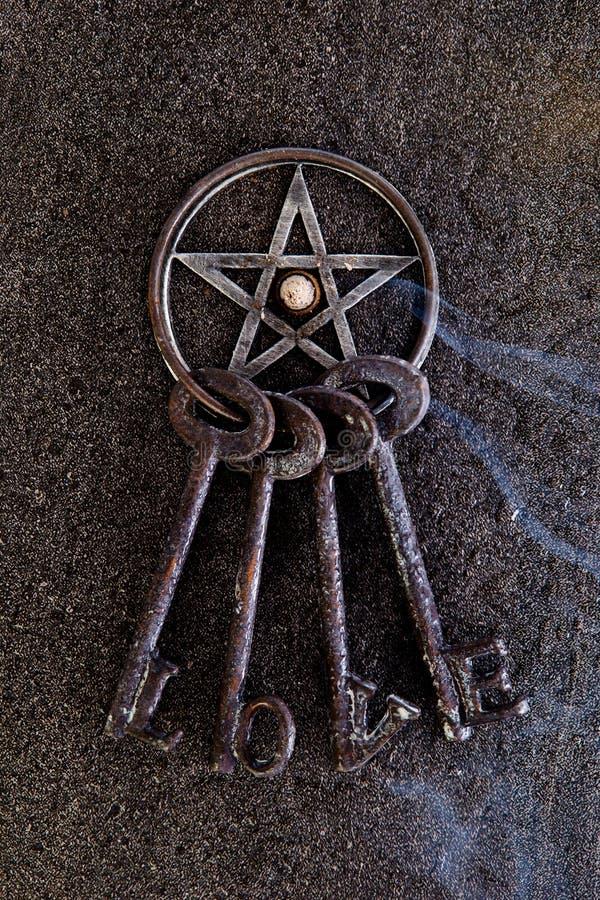 Wierook het branden in grijs metaal pentagram met liefdesleutelring op sla stock afbeeldingen