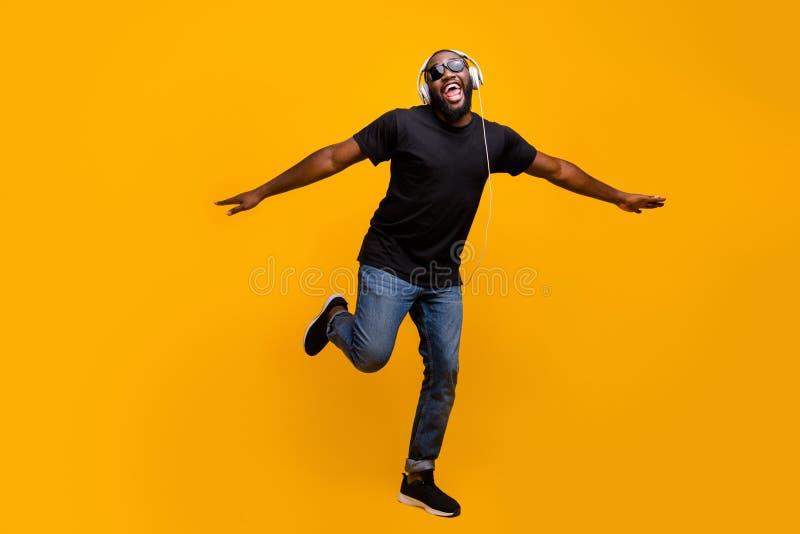 Wierzę, że mogę latać Pełne zdjęcie, zabawne pozytywne afro amerykański facet słucha muzyki z słuchawkami, śpiewają piosenki podn fotografia stock