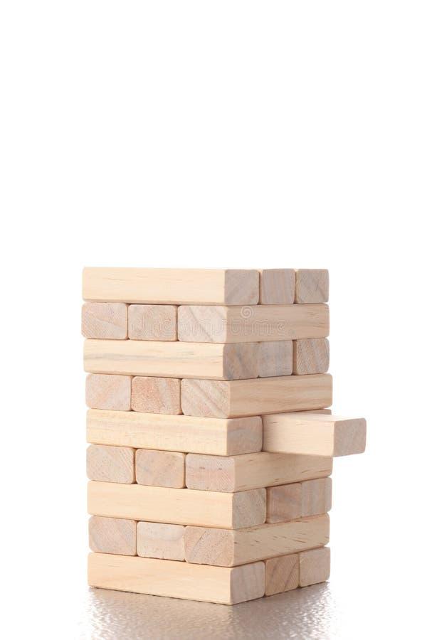 Wierza robić z zabawkarskimi drewnianymi blokami z jeden blokowy nadchodzącym za białym tle z kopii przestrzenią dla twój te obraz royalty free