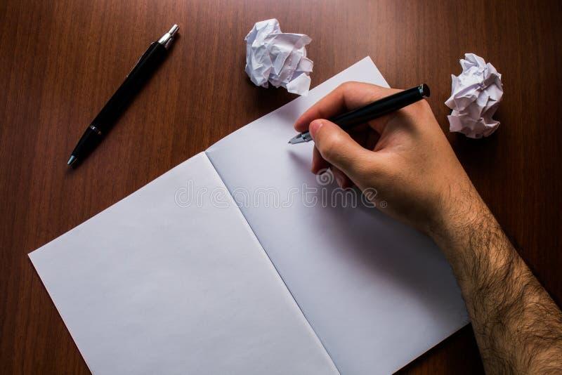 Wierzch zamknięty w górę widoku notatnika mężczyzny otwartej ręki pisze mienia pióru małych papierowych piłkach kłama drewnianego zdjęcia stock