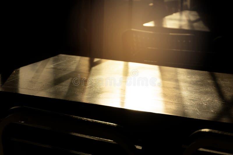 Wierzchołek drewno stół z pomarańczowym ranku światłem słonecznym w restauracyjnym ciemnego pokoju wnętrza tle obrazy royalty free