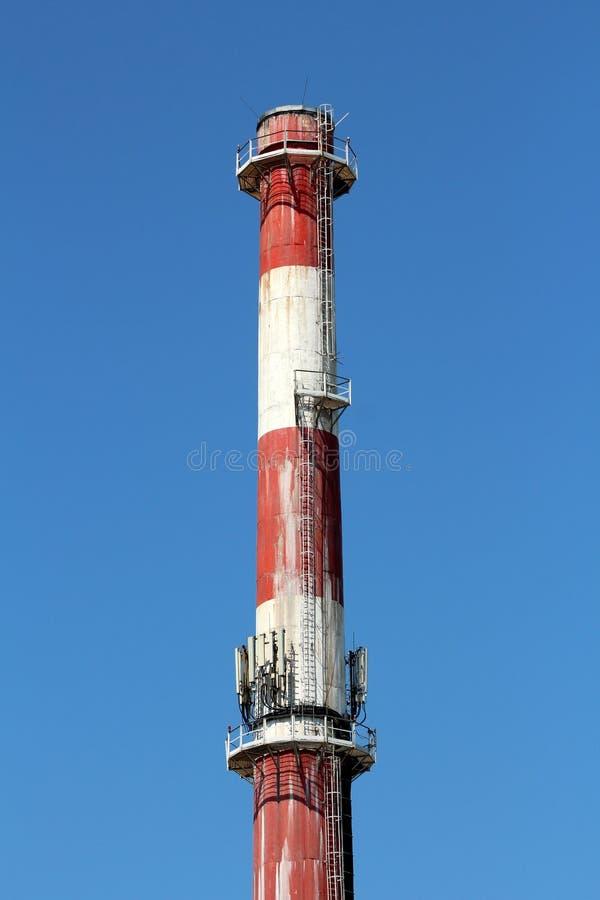 Wierzchołek wysoki przemysłowy czerwieni i bielu komin z wieloskładnikowymi telefon komórkowy antenami zdjęcia royalty free