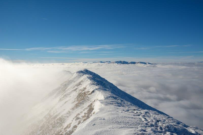 Wierzchołek wysokie góry, zakrywający śniegiem i mgłą zdjęcia stock