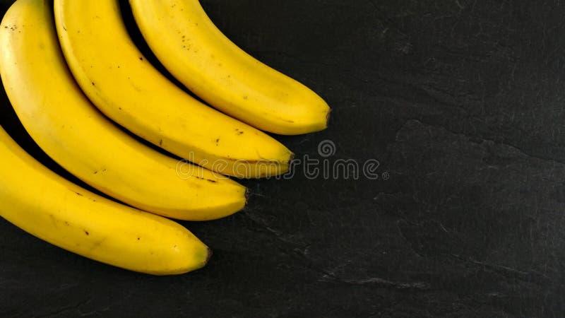 Wierzchołka puszka widok, cztery banana na czerń łupku desce, przestrzeń dla teksta na prawej stronie obrazy stock