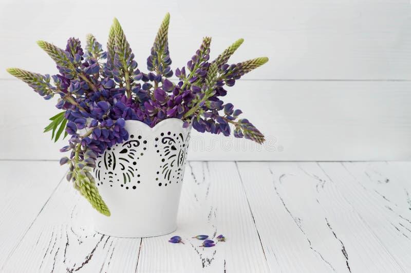 Wiese blüht Lupinesblumenstrauß im weißen dekorativen Eimer stockfoto