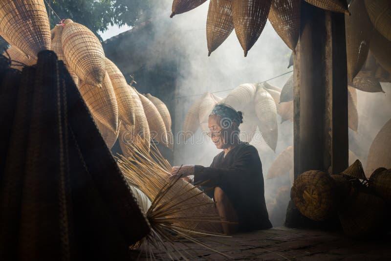 Wieszający jen Wietnam, Lipiec, - 9, 2016: Stary domowy jard z wiele bambusowy rybi oklepa i kobiety rzemieślnik robi tradycyjnem obraz stock