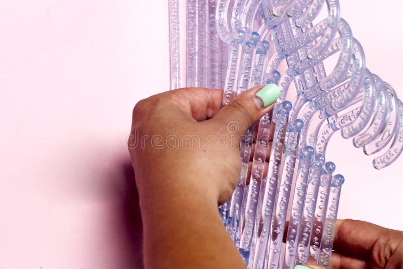 Wieszaki w żeńskich rękach na kolorowym różowym tle obraz stock