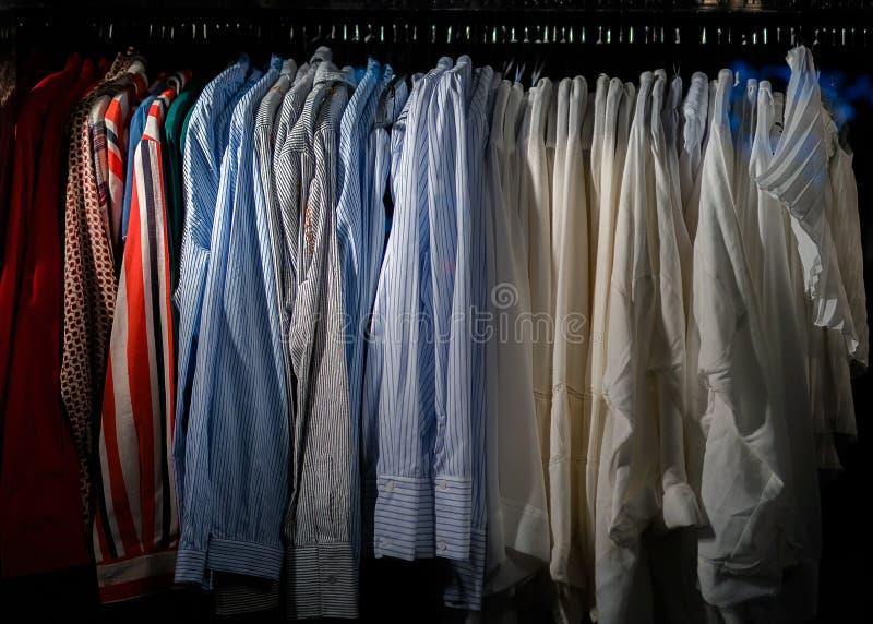 Wieszaki z różnym odziewają w szafie - garderoba pełno odziewa zdjęcia stock