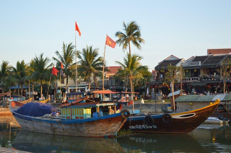 Wietnam, Hoi - Sceniczny wielkie łodzie rybackie na Thu bonu rzece przy zmierzchem i quayside obrazy stock