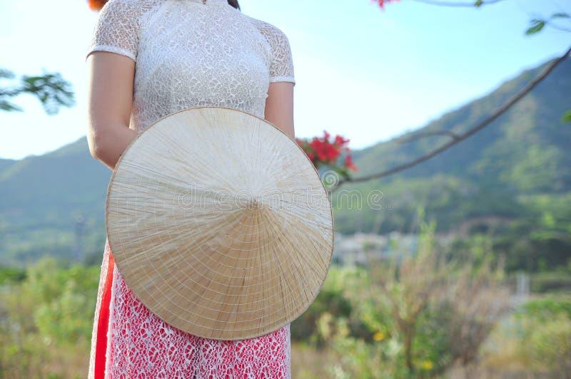 Wietnamczyk długa suknia z tradycyjnym liścia kapeluszem obraz royalty free