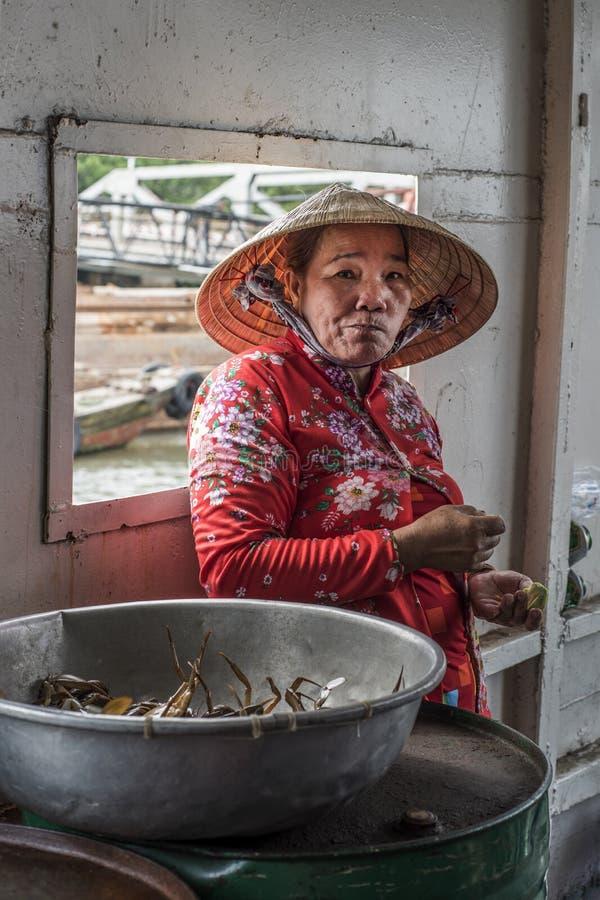 Wietnamscy kraba sprzedawcy spojrzenia przy kamerą podczas gdy krzyżujący Mekong rzekę w promu w południowym Wietnam obraz royalty free