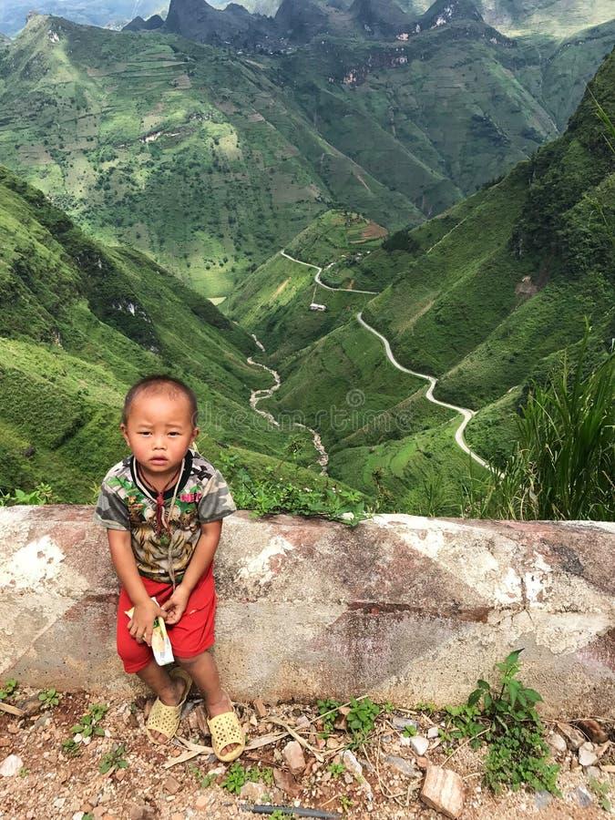 Wietnamska chłopiec siedzi przed sławnymi podróży miejsc przeznaczenia ryż p obrazy stock