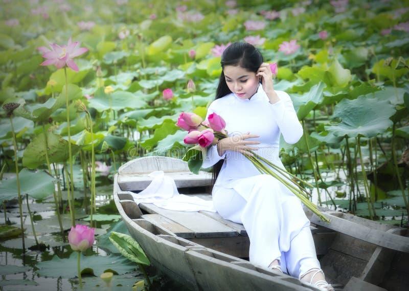 Wietnamska dziewczyna w tradycyjnej długiej sukni lub Ao Dai wśrodku łodzi obrazy royalty free