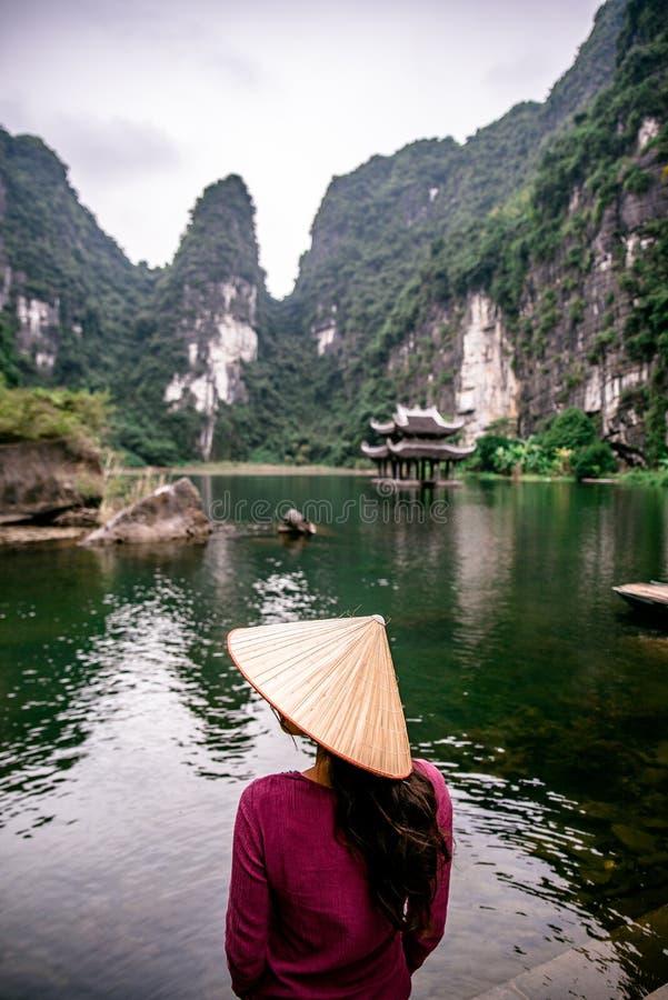 Wietnamska dziewczyna z słomianym kapeluszem w Trang Sceniczny krajobraz tworzyłem krasem góruje i zasadza wzdłuż rzeki (UNESCO ś zdjęcie royalty free
