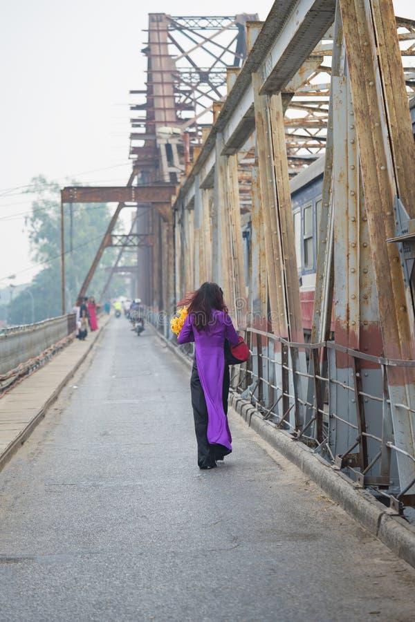 Wietnamska kobieta w tradycyjnym sukni Ao Dai odprowadzeniu na starym Długim Bien moscie, Hanoi miasto zdjęcie stock
