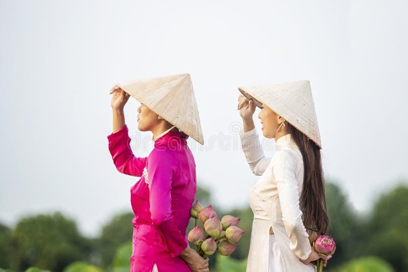 Wietnamska kobiety grupa na drewnianym ??dkowatym azjacie dwa kobiet stojak zbierać lotosowych kwiaty na drewnianej łodzi pi?kna  zdjęcie stock