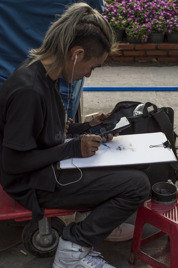 Wietnamski artysta rysuje portret od wizerunku na jego mobilnej fotografii w ulicie Ho Chi Minh miasto, Wietnam zdjęcia royalty free
