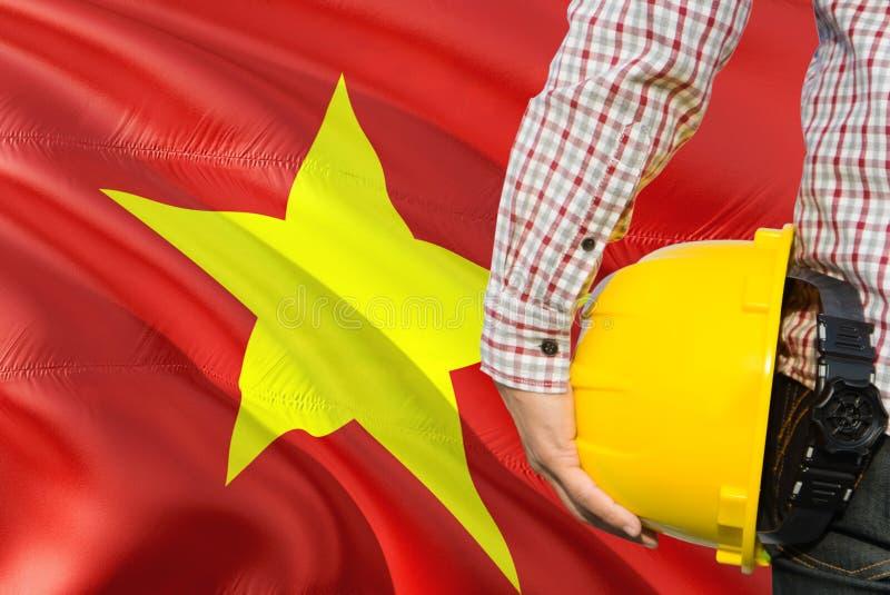 Wietnamski inżynier trzyma żółtego zbawczego hełm z machać Wietnam chorągwianego tło Budowy i budynku poj?cie obrazy royalty free