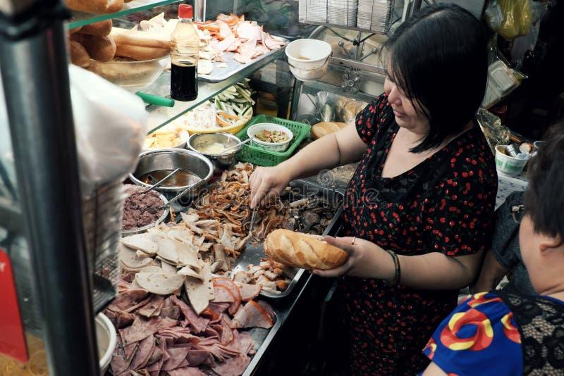 Wietnamski kobieta bubla Wietnam chleb na furze przy nocy ulicy jedzeniem fotografia stock