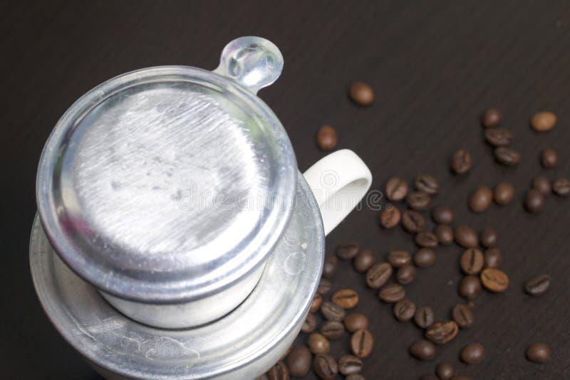 Wietnamski piwowar dla kawy w gromadzić formie stoi na białej filiżance Następnie rozrzucone kawowe fasole obraz stock