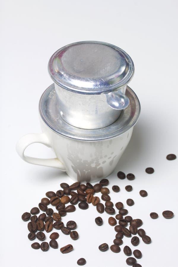 Wietnamski piwowar dla kawy w gromadzić formie stoi na białej filiżance Następnie rozrzucone kawowe fasole obrazy stock