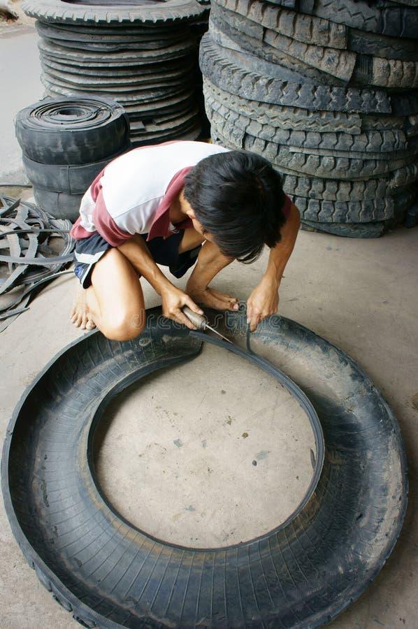 Wietnamski pracownik, przetwarza oponę, opona zdjęcie royalty free