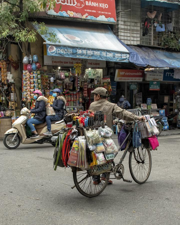 Wietnamski sprzedawca uliczny w Hanoi, na rowerowych przewożenie towarach dla sprzedaży obrazy stock