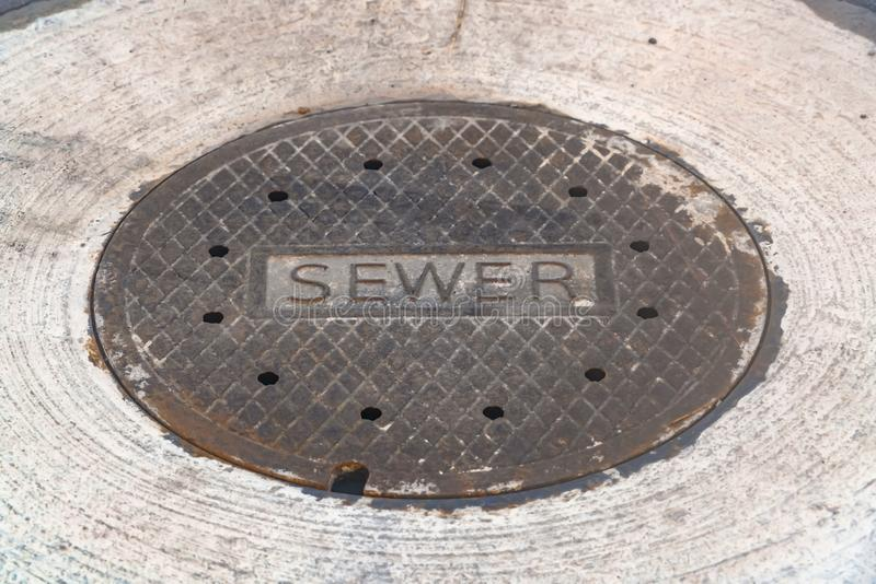 Wietrzejąca ściekowa manhole pokrywa na drodze zdjęcie royalty free
