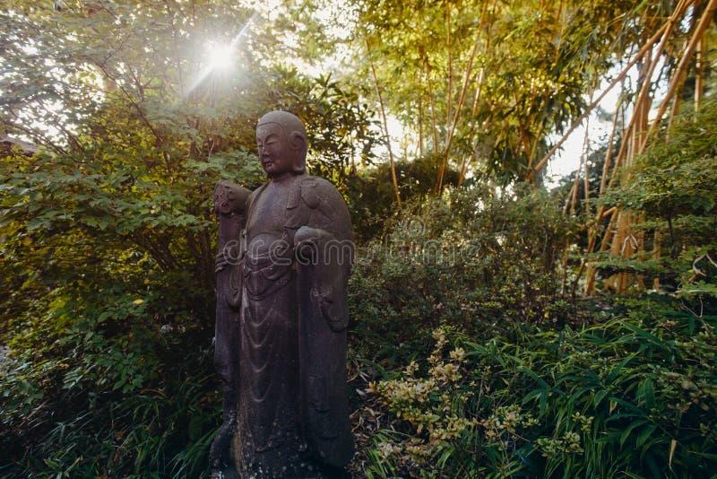 Wietrzejąca, naturalnych rozmiarów kamienna statua mnich buddyjski, medytuje pod zielenią fotografia stock