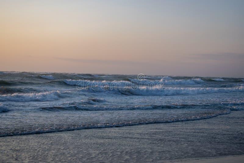 Wietrzny zmierzch przy plażą Løkken Dani Północny region Kolorowy i markotny niebo Fale od ses obrazy royalty free