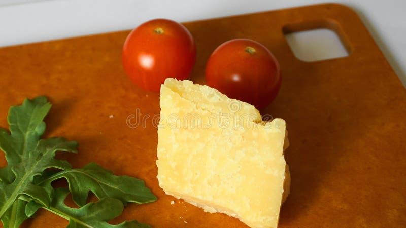 ?wiezi zieleni arugula li?cie, czere?niowi pomidory i parmesan ser na hardboard, obrazy royalty free