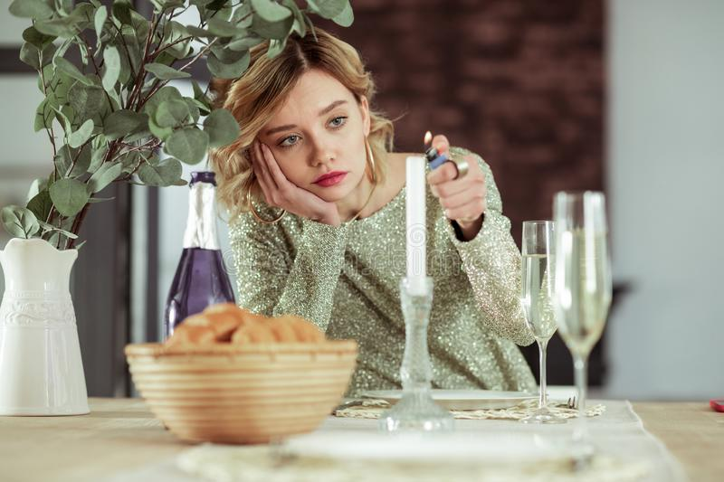 Wife burning the candle while feeling sad staying alone. Burning candle. Blonde-haired elegant wife burning the candle while feeling sad staying alone royalty free stock photo